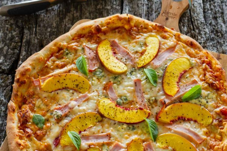 A medium size peach pizza, hot out of the oven